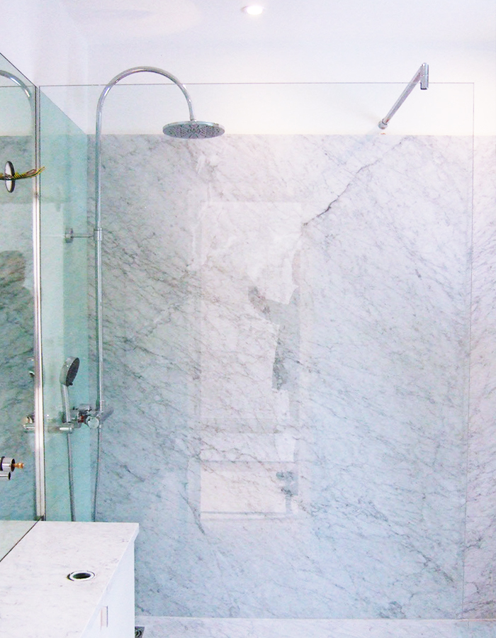walk-in shower with glass and marble